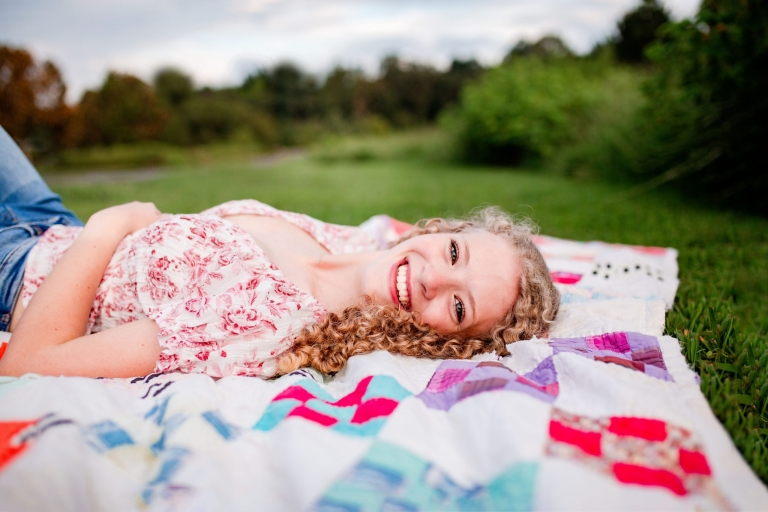 photo of a blonde curly haired high school senior laying on a colorful blanket in the grass.